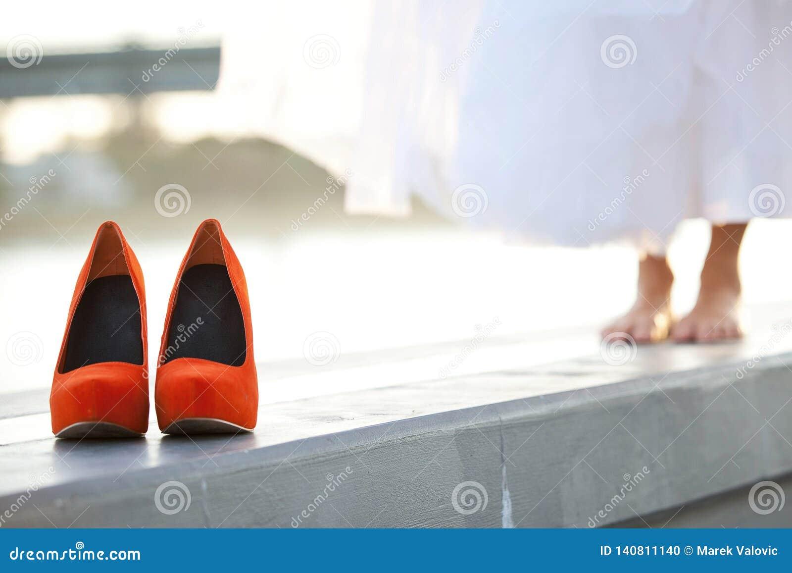 Zapatos que se casan Rojo-anaranjados delante de la novia descalza