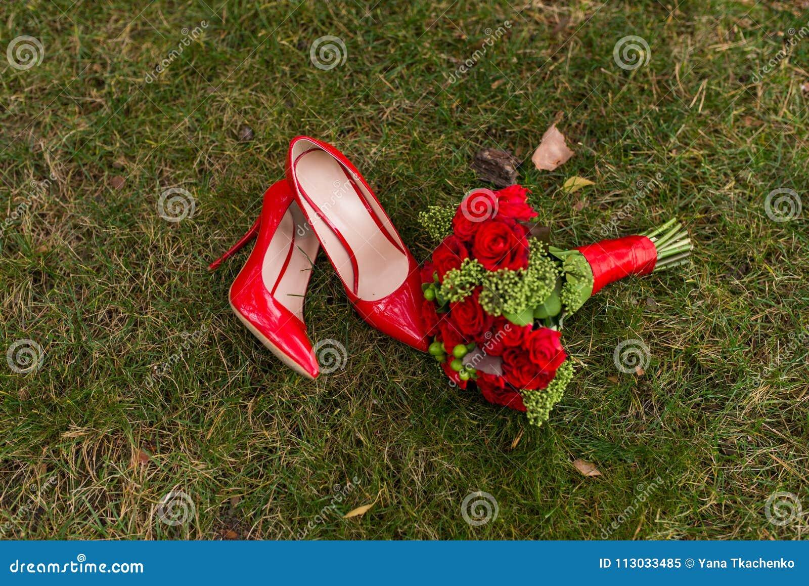 Zapatos rojos de la boda de la moda femenina con el ramo del ` s de la novia de rosas rojas y de bayas verdes en fondo de la hier