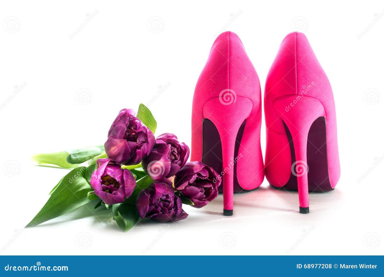 Zapatos rosados y tulipanes del tacón alto de las señoras aislados en blanco, para el lo