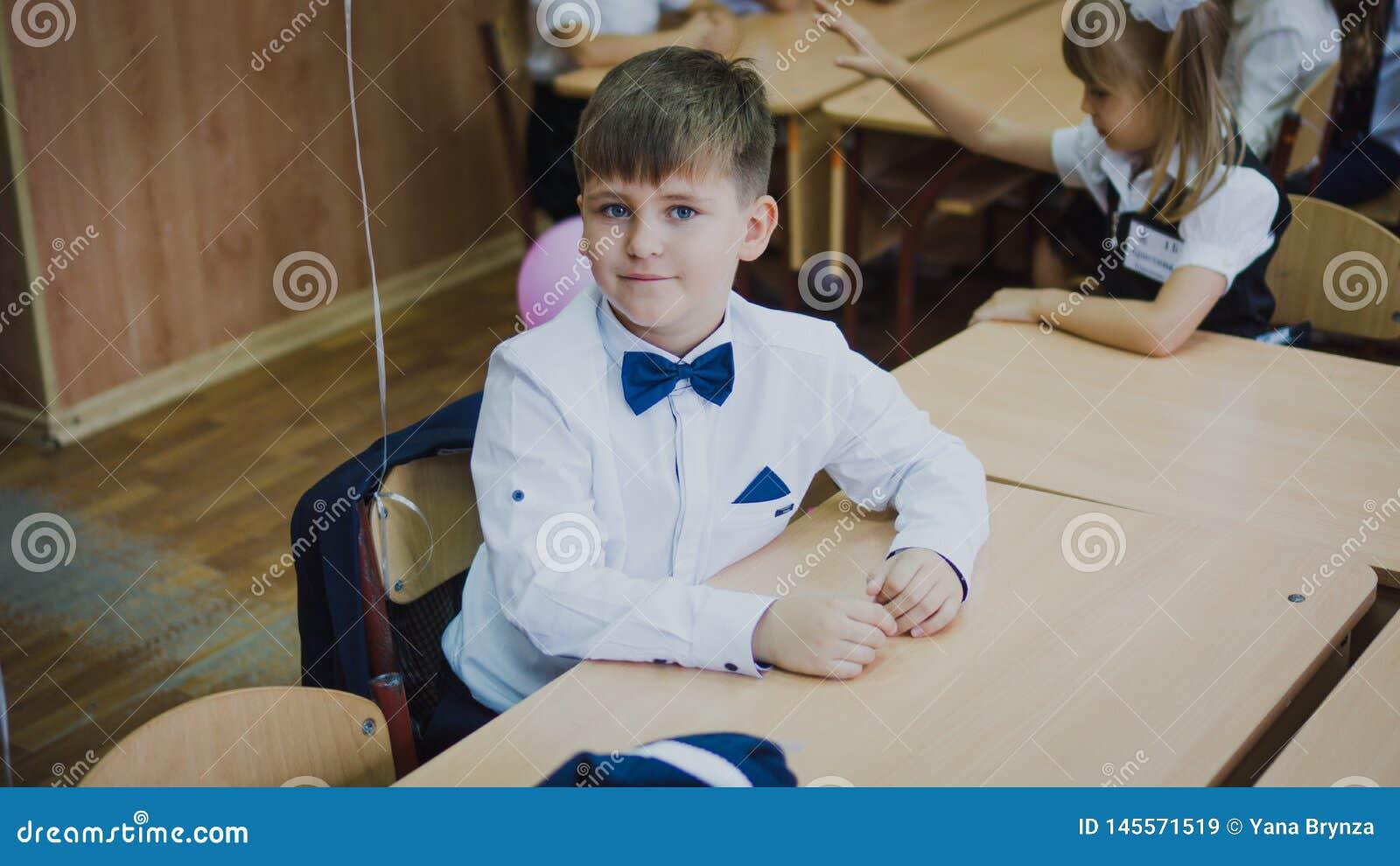 Zaporozhye, Украина - 1-ое сентября 2018: портрет первого грейдера в белой рубашке и голубой бабочке сидя на столе в a