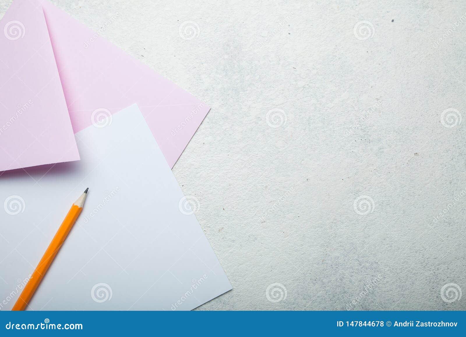 Zaproszenie ślub lub wakacje Tapetuje, różowa koperta i ołówek na białym rocznika biurku, przestrzeń dla teksta