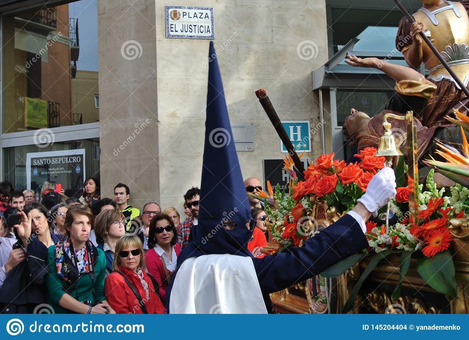 Man in a traditional costume covering his face beats a bell during the traditional Easter procession of Semanа Santa