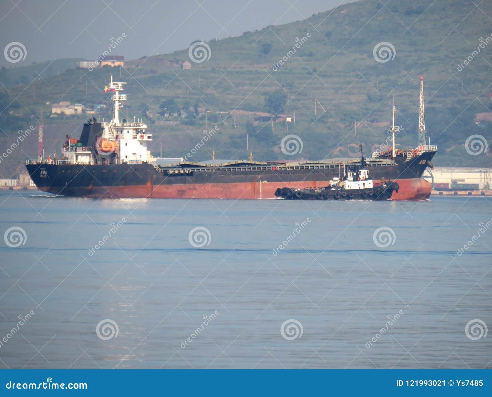 Zarubino Primorsky kray/Ρωσία - 22 Ιουλίου 2018: Γενική πρόσδεση φορτηγών πλοίων και tugboat στο λιμένα