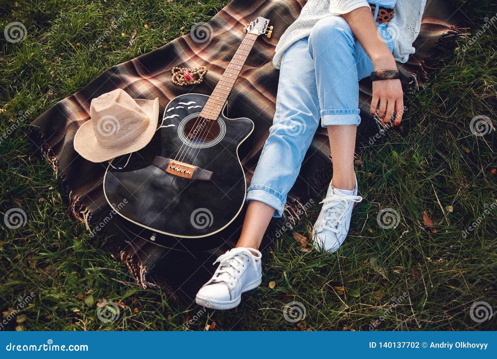 Zasięrzutny widok piękna kobieta odpoczywa na zielonym gazonie z gitarą Odgórny widok