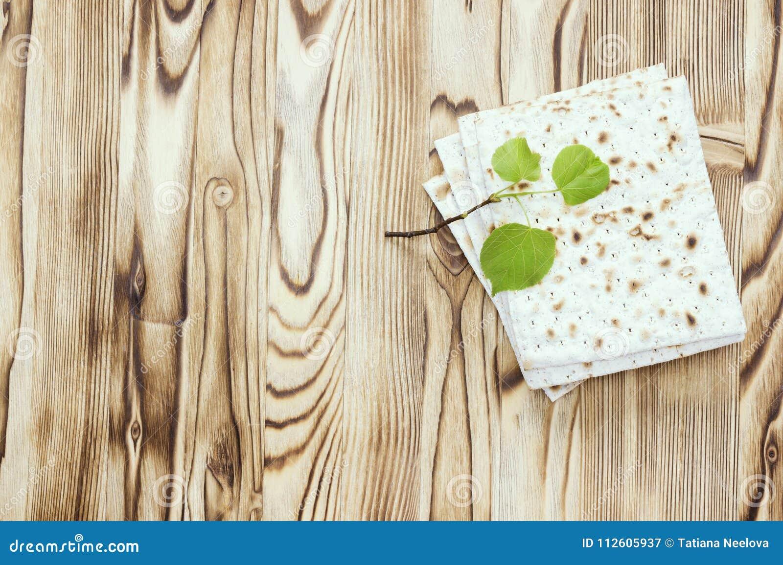 Zasięrzutna fotografia kawałki i małej wiosny świeża lipowa gałąź matzah lub matza Matzah na drewnianym stole dla Żydowskiego
