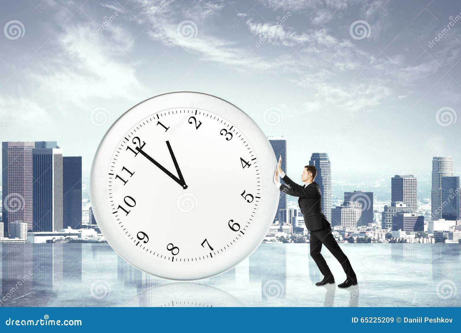 Zatrzymuje synchronizować pojęcie z biznesmenem pcha dużego zegar przy miasto b