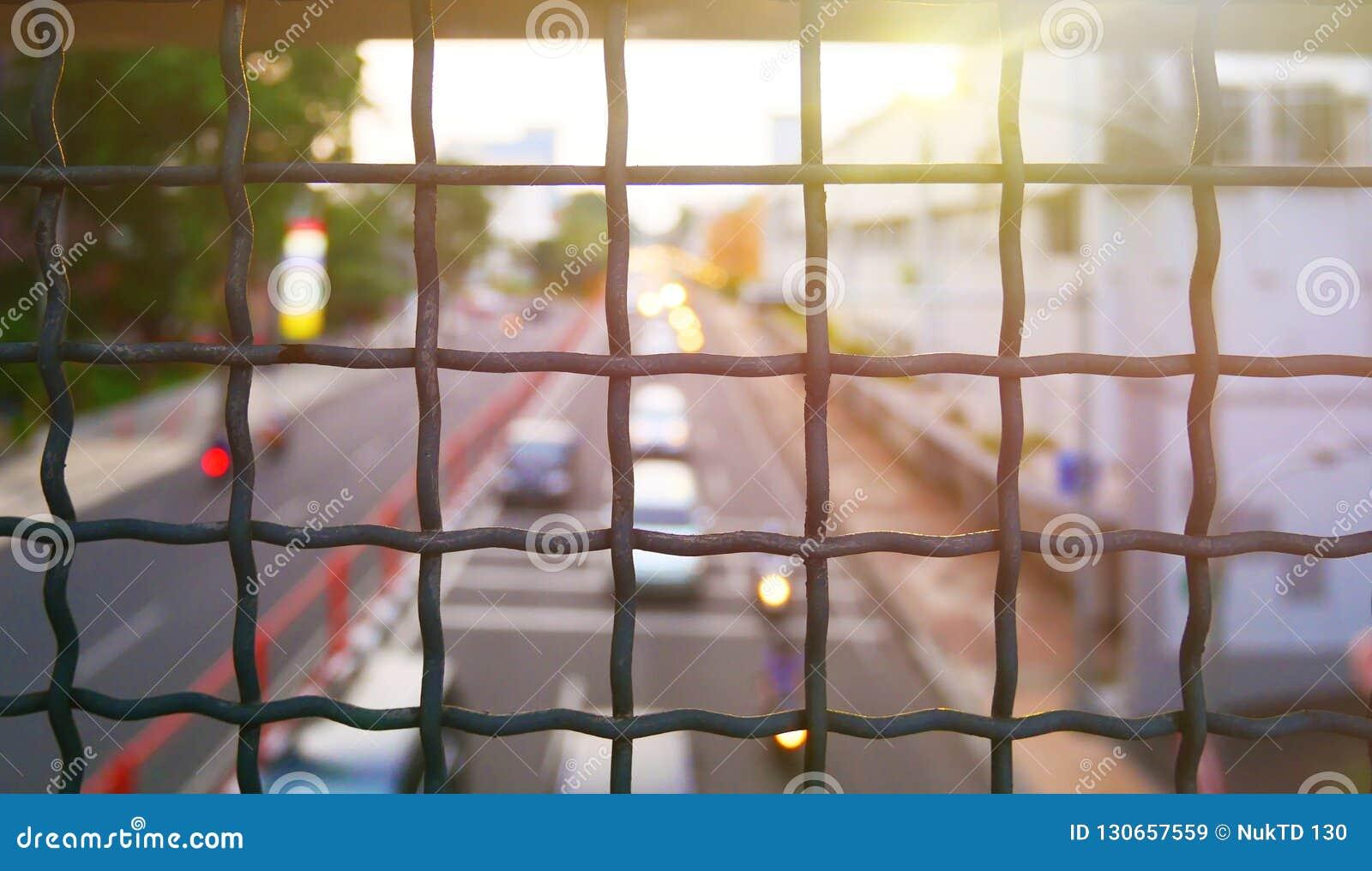 Zaun mit Metallgitter und Voraufflackern im Hintergrund