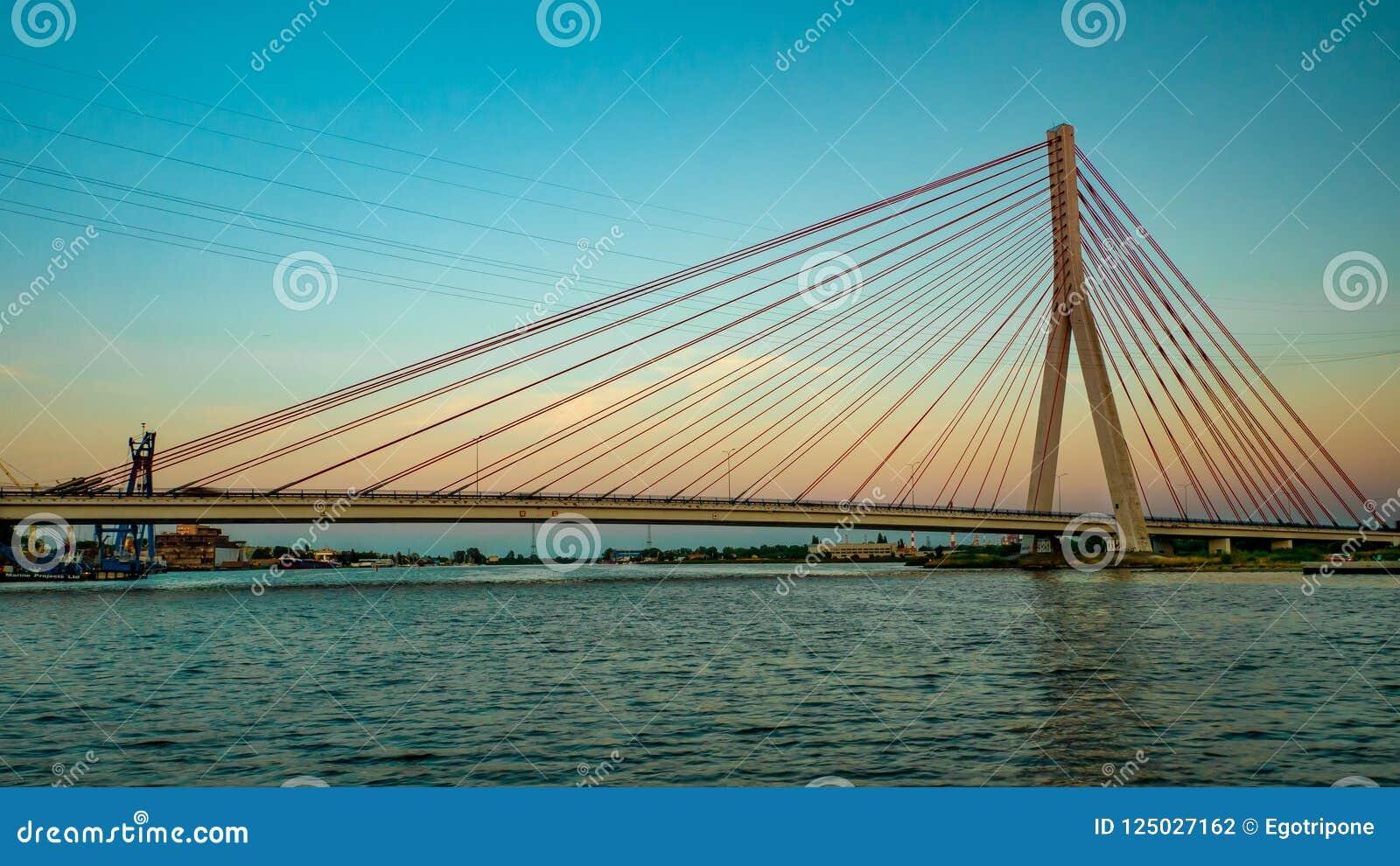 Zawieszenie most nad rzeką przy zmierzchem