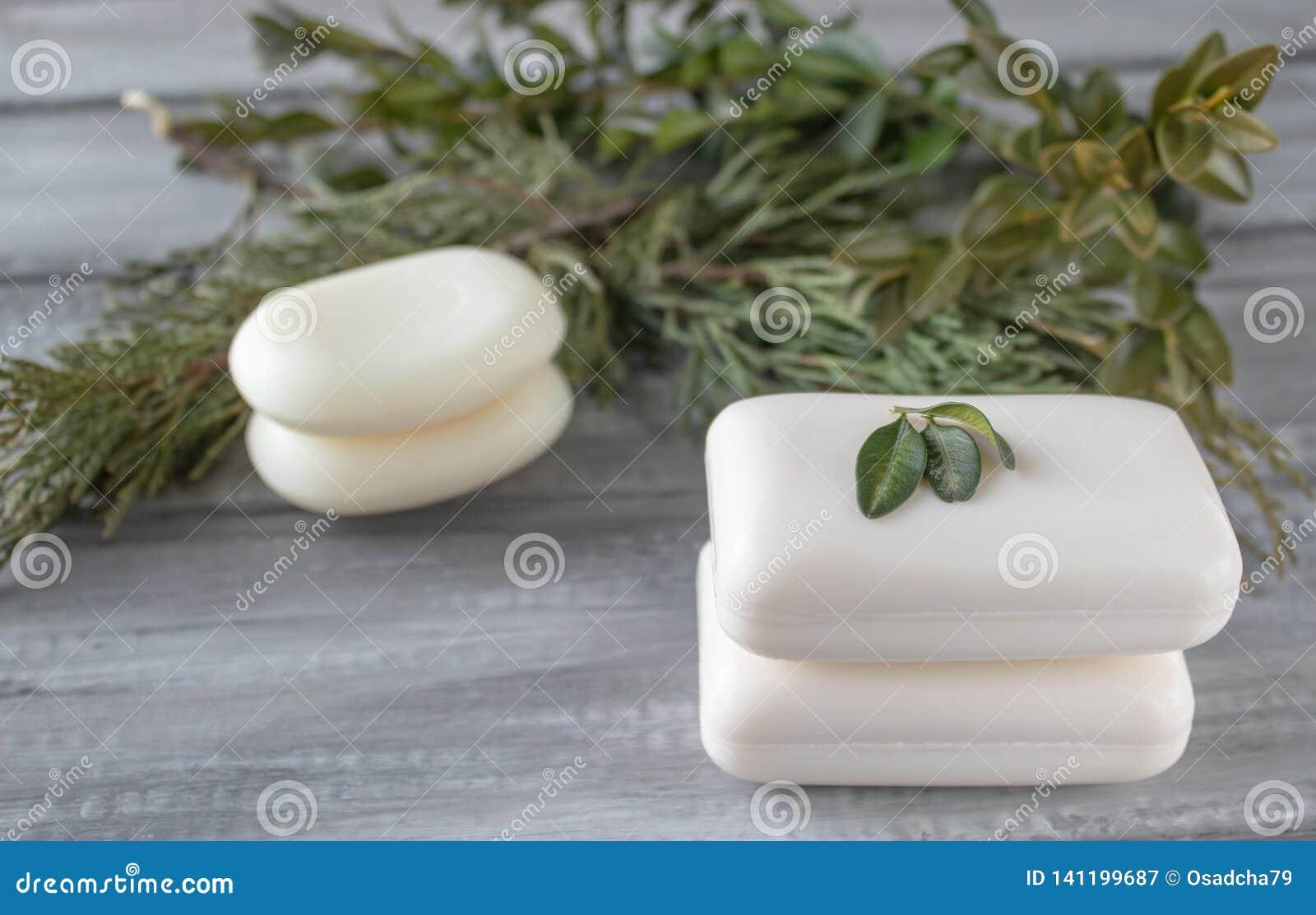 Zbliżenie bielu mydło na drewnianym stole z zielonymi gałąź