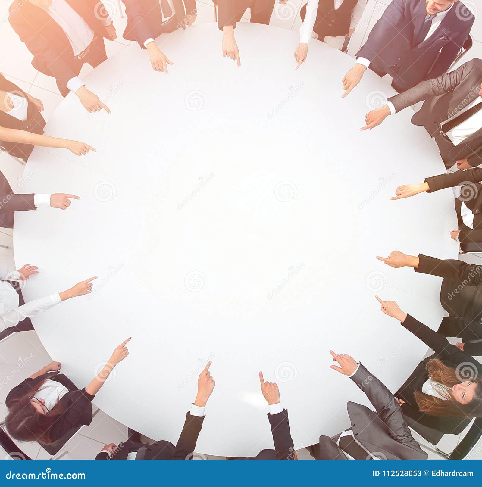Zbliżenie biznesu drużynowy wskazywać w centrum stół