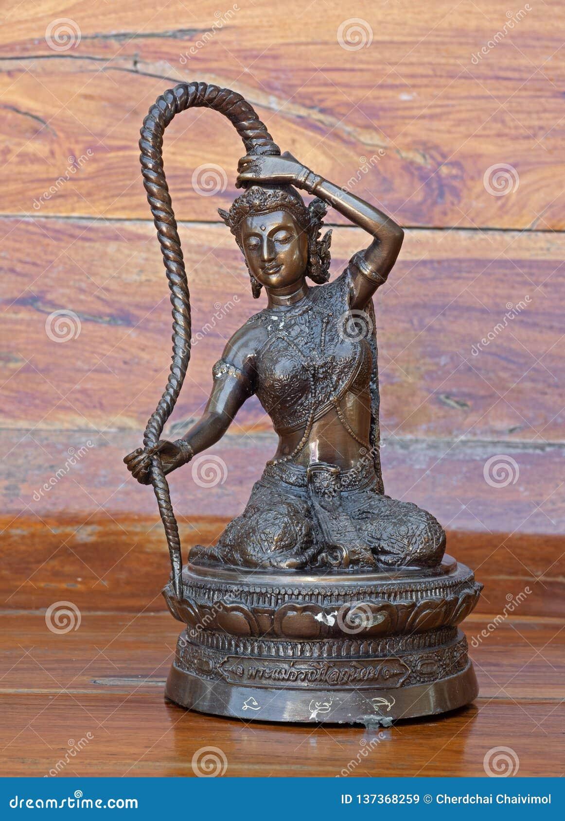 Zbliżenie bogini statua Phra Mae Thorani Odizolowywający na Drewnianym tle