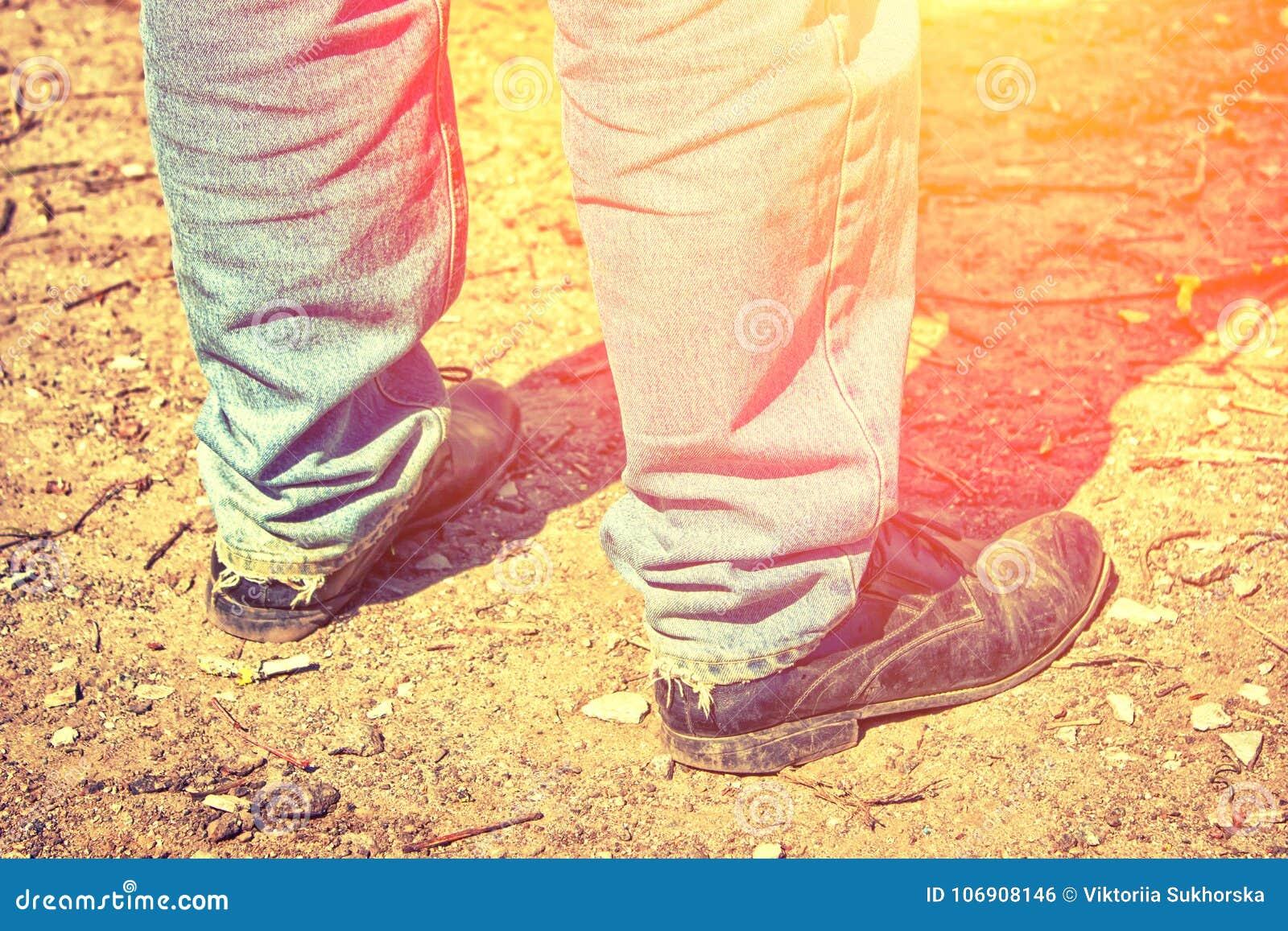 Zbliżenie cieki mężczyzna w starych niebieskich dżinsach i będących ubranym butach T