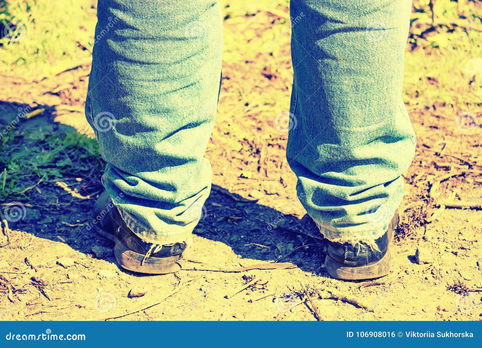 Zbliżenie cieki mężczyzna w starych niebieskich dżinsach i starych butach tinted
