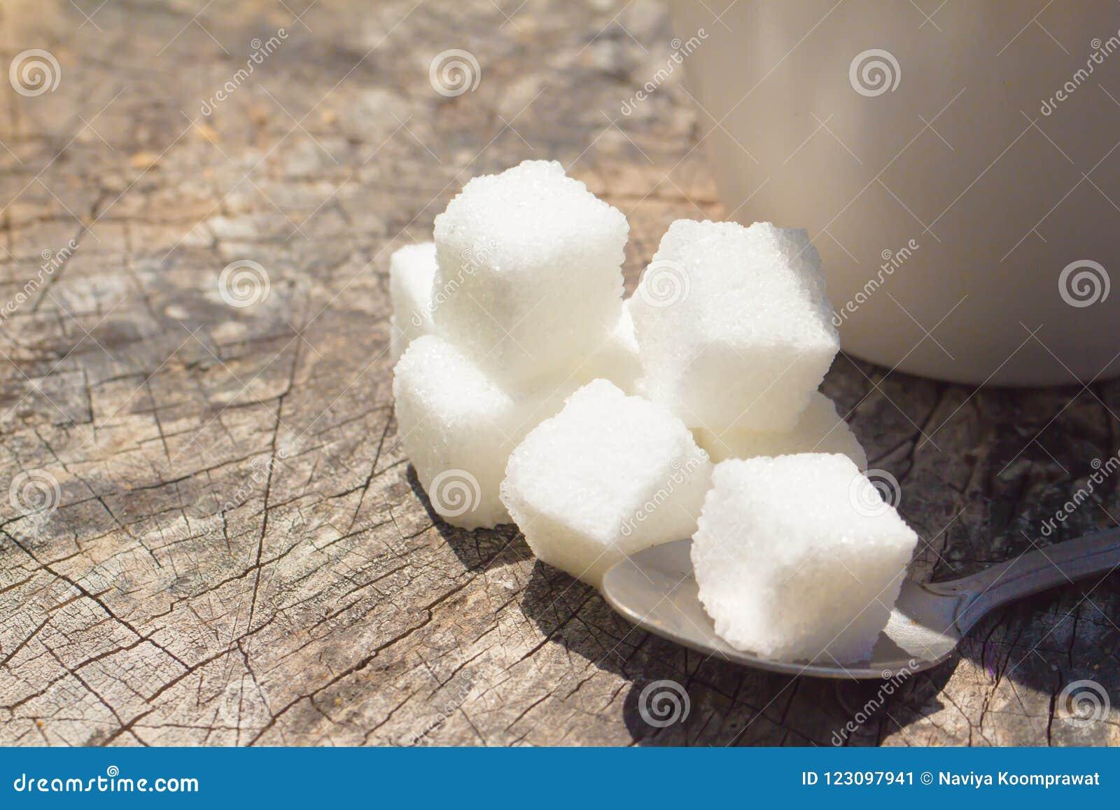 Zbliżenie cukrowi sześciany z herbacianą łyżką