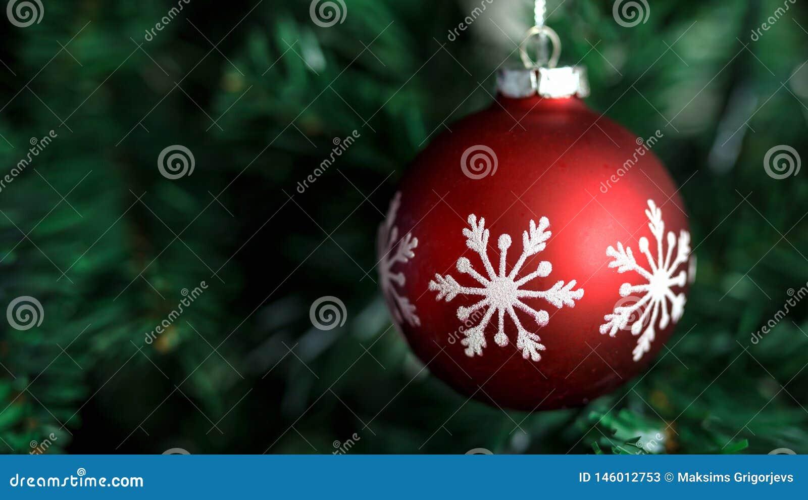 Zbliżenie czerwony bauble obwieszenie na dekorującym bożych narodzeń i nowego roku drzewie