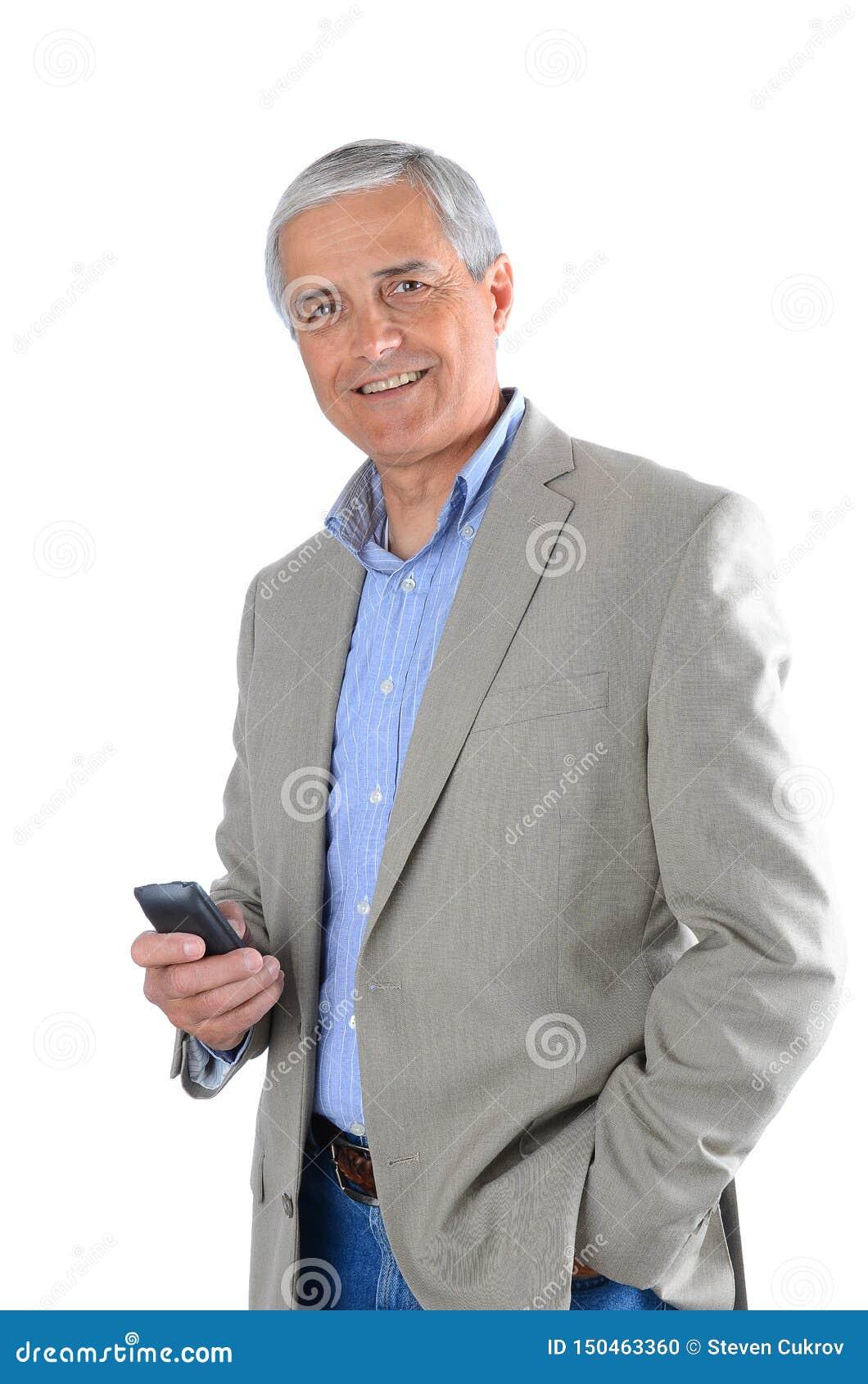 Zbliżenie dojrzały biznesmen niezobowiązująco ubierał i trzymający komórkowego przyrząd w jego ręce