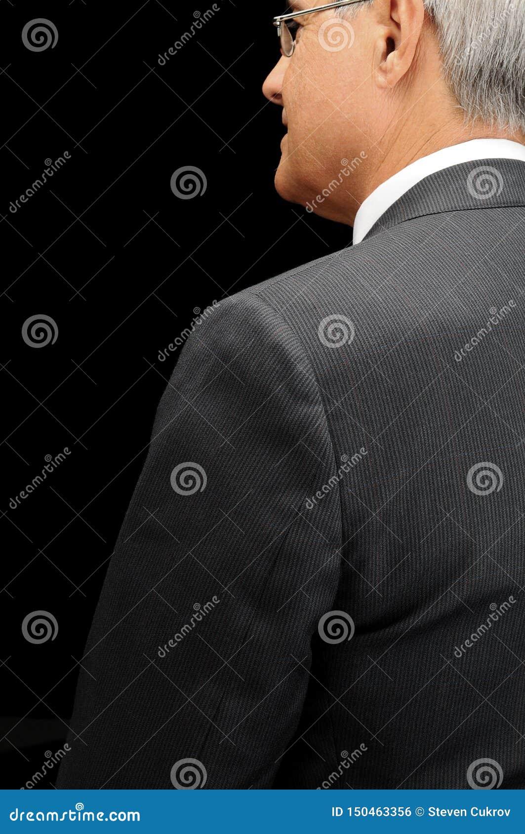 Zbliżenie dojrzały biznesmen widzieć od profilu nad czarnym tłem za w