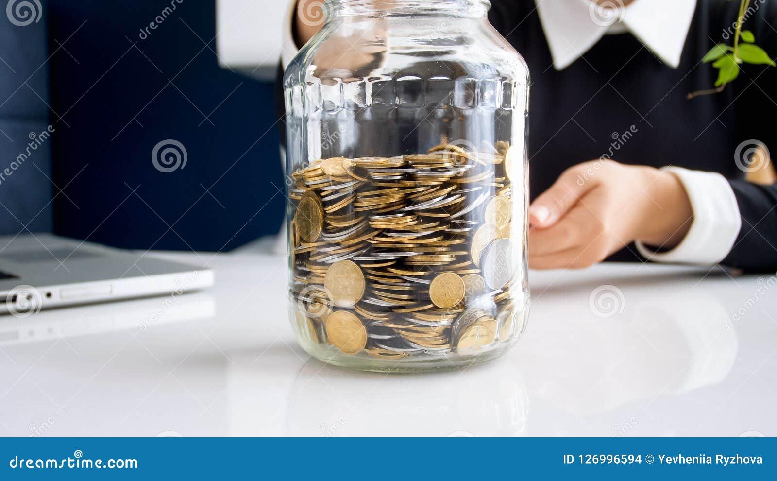 Zbliżenie fotografia młode bizneswomanu kładzenia monety w szklanym słoju