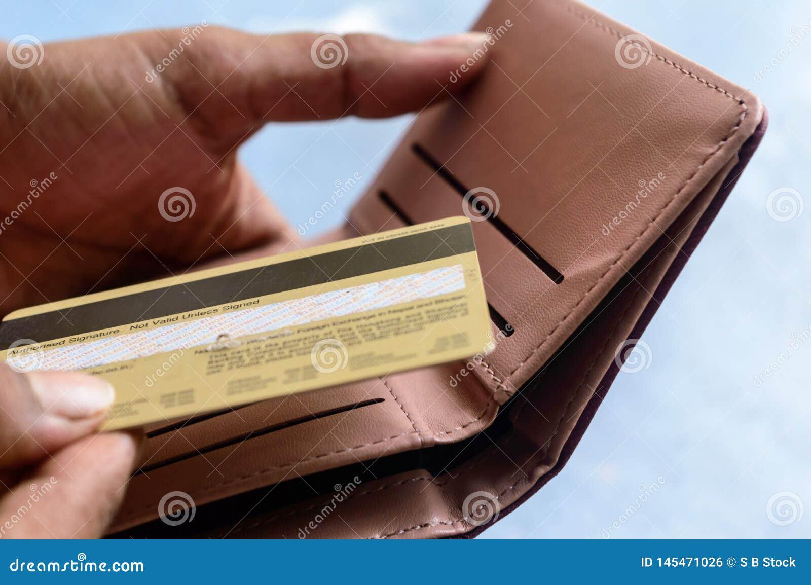 Zbliżenie fotografia młody bizneswomanu kładzenie, płacić z kartą kredytową w rzemiennym portflu na białym tle lub brać za lub