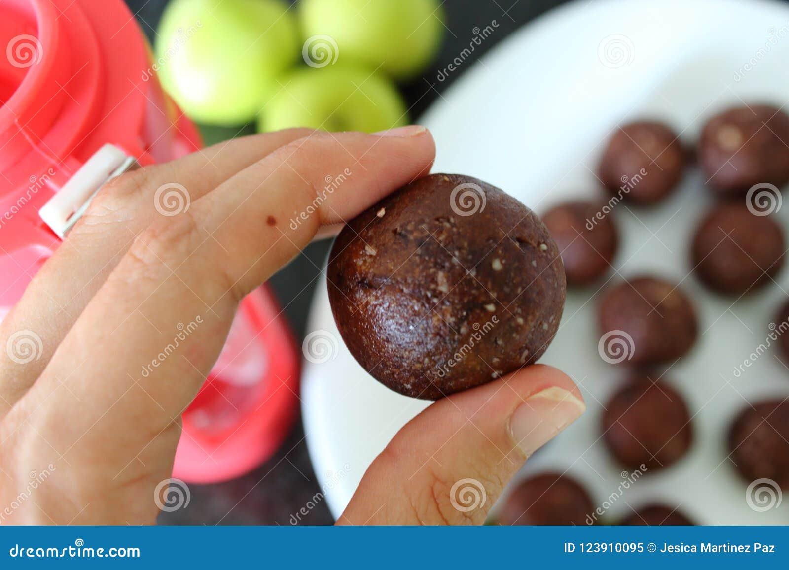 Zbliżenie kobiety ` s ręki whith zdrowy cukierki taktuje Kulinarne czekoladowe energetyczne piłki z migdałami