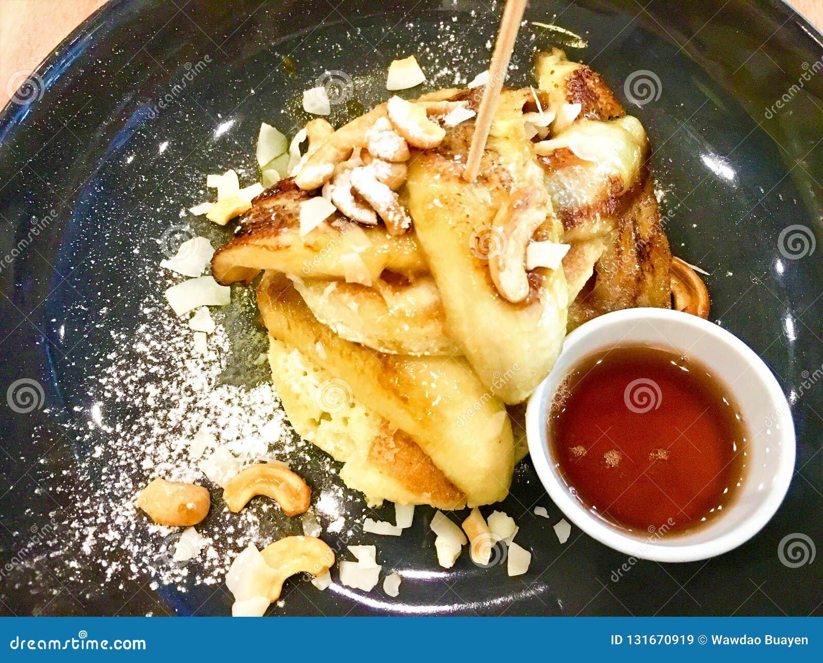 Zbliżenie Kokosowy blin Koks z blinem słuzyć z bananową karmelu i nerkodrzewu dokrętką Na stole