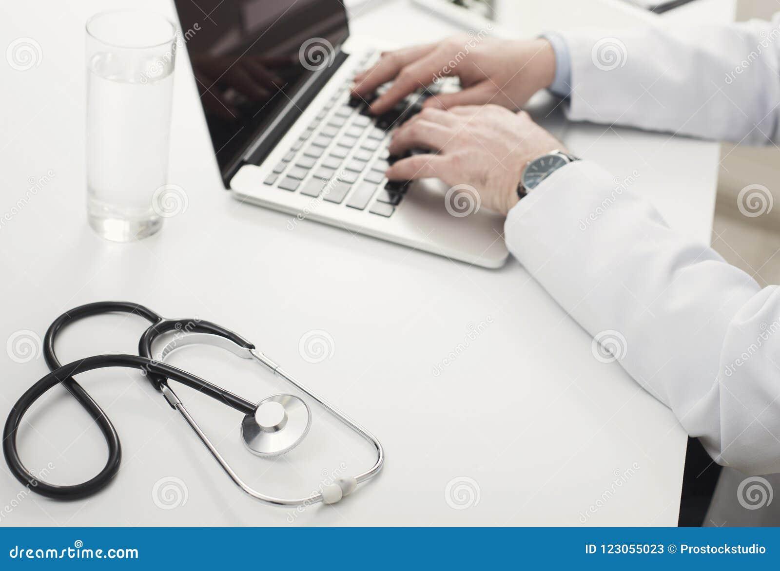 Zbliżenie lekarek ręki na laptop klawiaturze