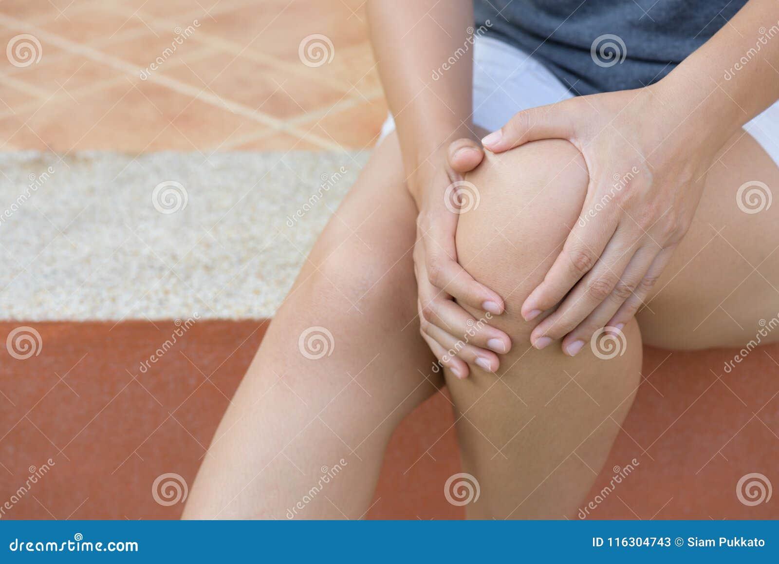 Zbliżenie młodej kobiety uczucia ból w jej kolanie w domu