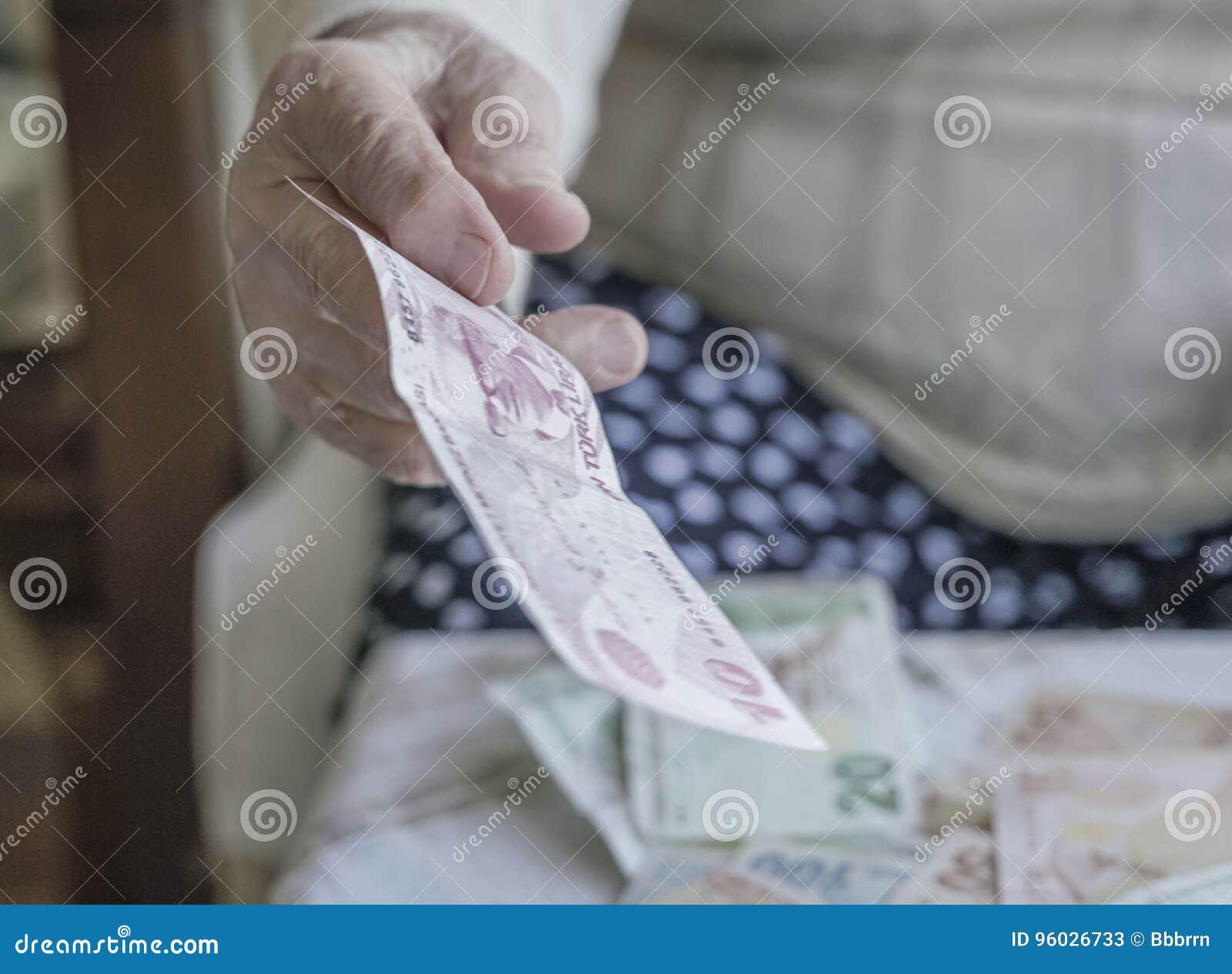 Zbliżenie marszcząca ręka trzyma tureckiego lira banknoty