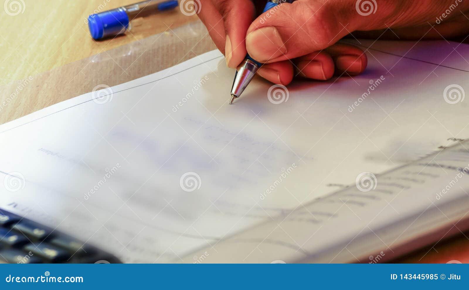Zbliżenie men& x27; s ręka która pisze coś na papierze z pomocą pióra