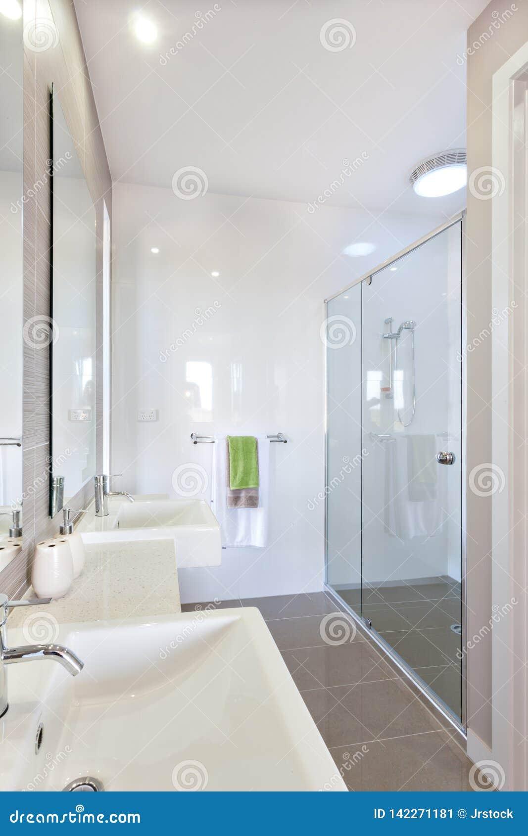 Zbliżenie nowożytny washstand z srebnego faucet pobliskim lustrem w washroom