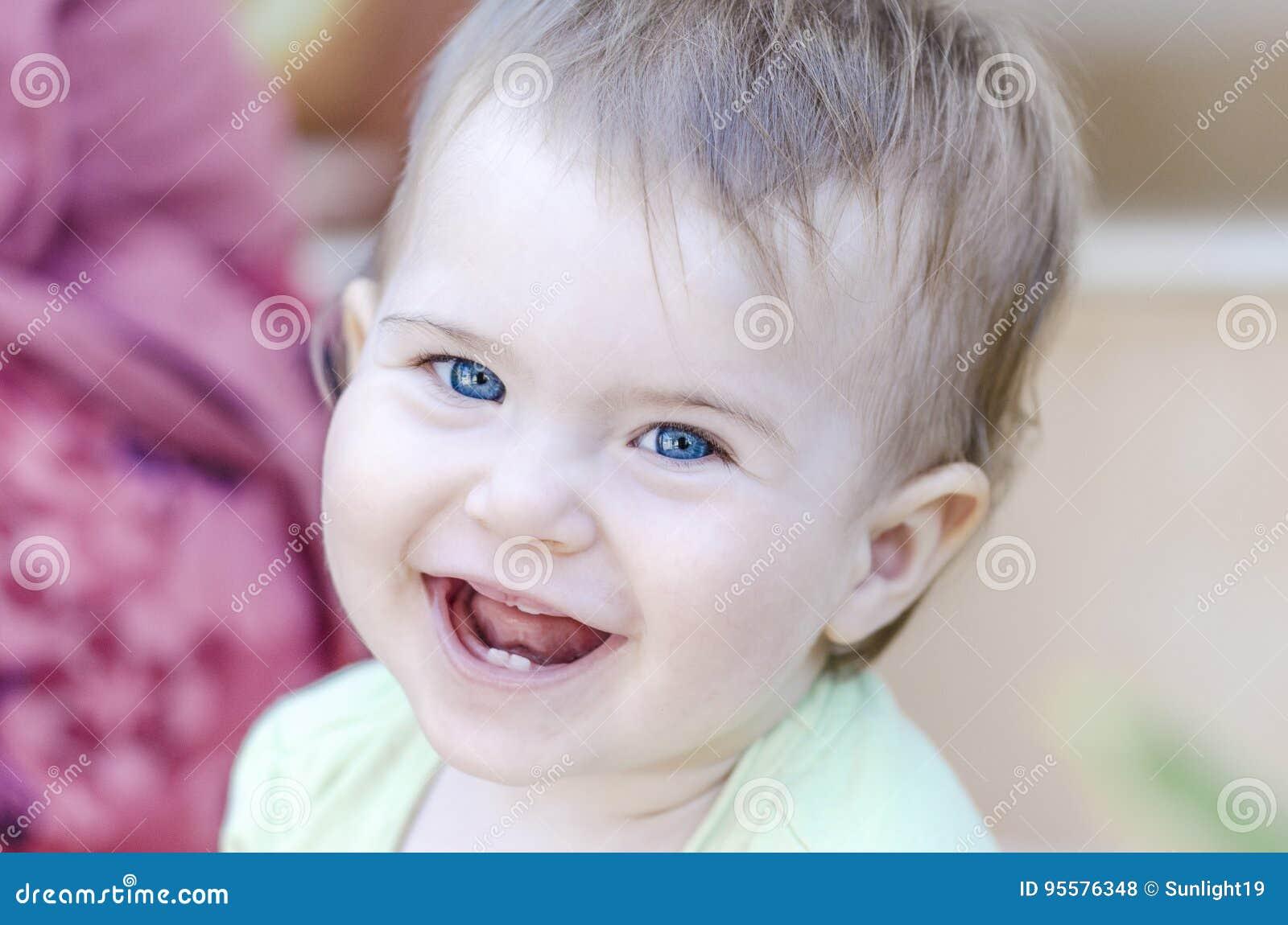 Zbliżenie ono uśmiecha się z jej pierwszy zębami szczęśliwy dziecko