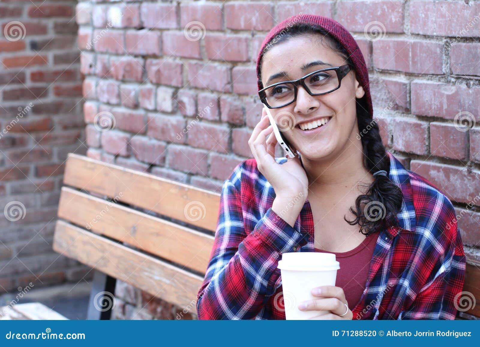 Zbliżenie plenerowy portret ślicznej szczęśliwej brunetki etniczna nastoletnia dziewczyna opowiada na smartphone z takeaway kawą