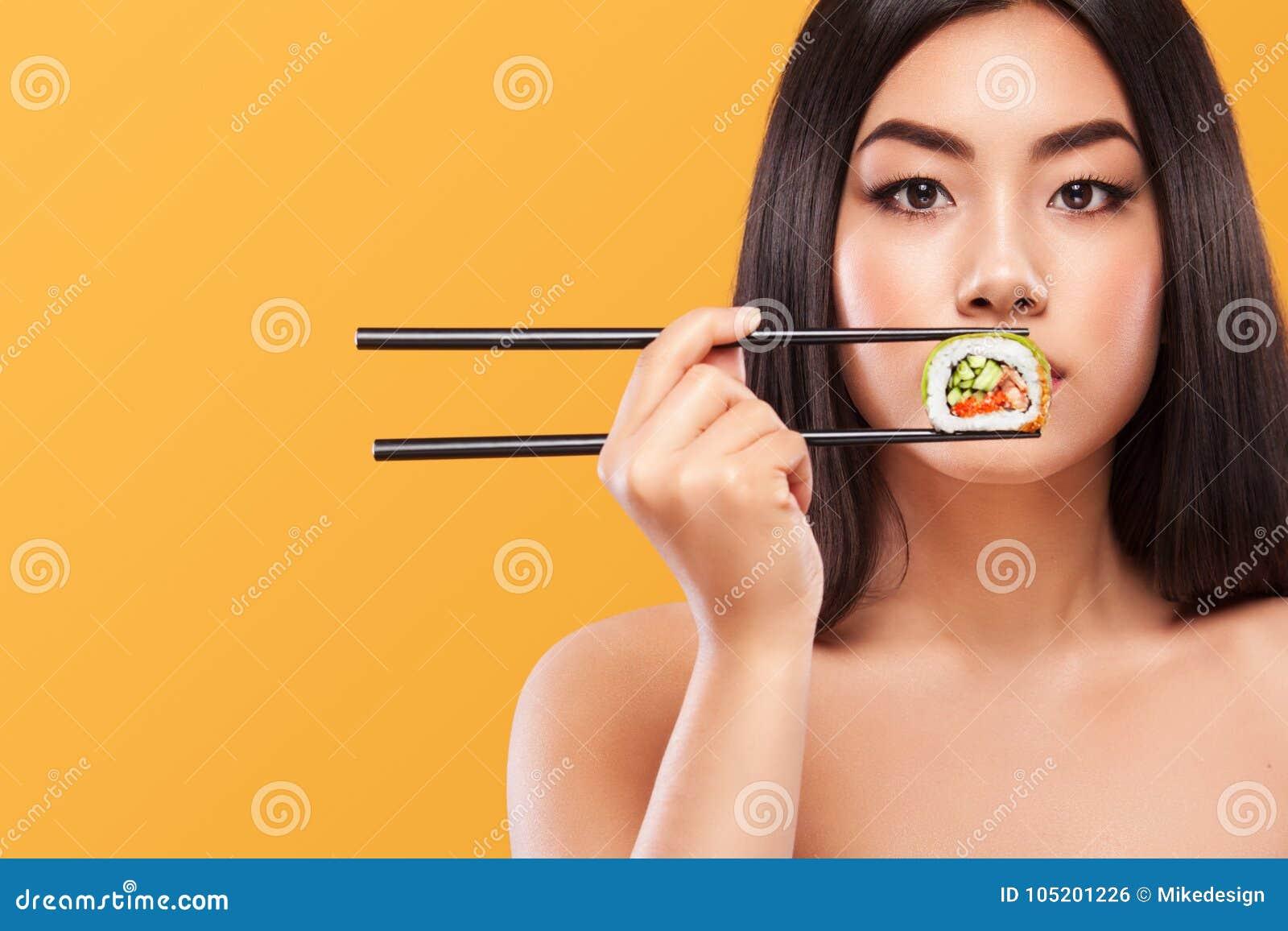 Zbliżenie portret azjatykci kobiety łasowania suszi i rolki na żółtym tle Copyspace