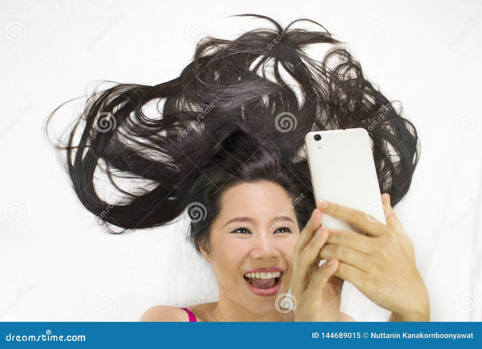 Zbliżenie portret azjatykcie kobiety kłama na ziemi z czarny długie włosy postępujący wow i kursujący telefon,