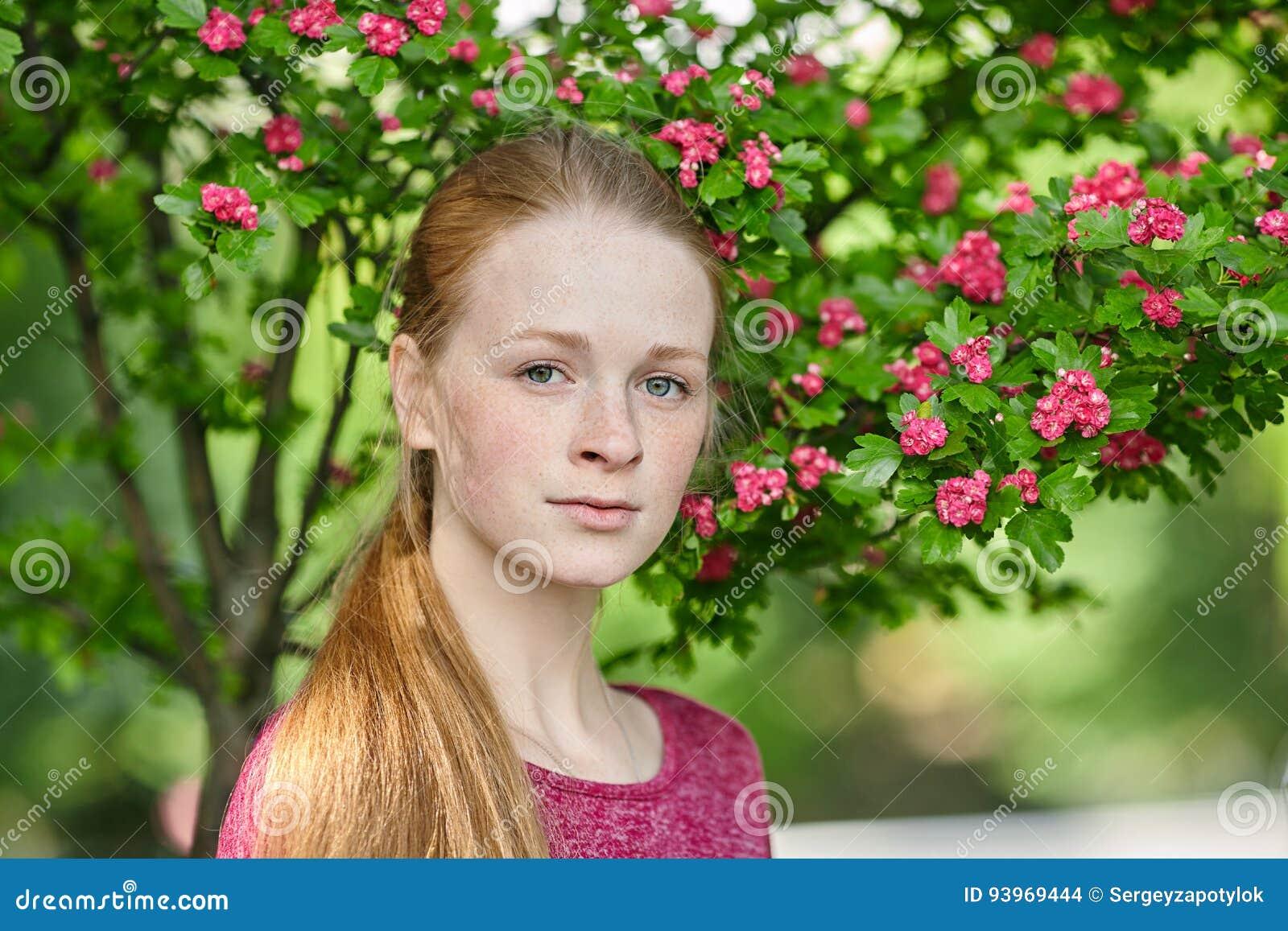 Zbliżenie portret młoda naturalna piękna rudzielec kobieta w fuksi bluzce pozuje przeciw kwitnąć drzewa z zamazanym zielonym fola