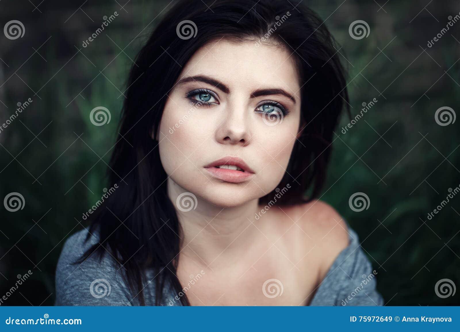Zbliżenie portret piękna młoda seksowna Kaukaska kobieta z czerwonym czarni włosy, niebieskie oczy, patrzeje w kamerze na zmierzc
