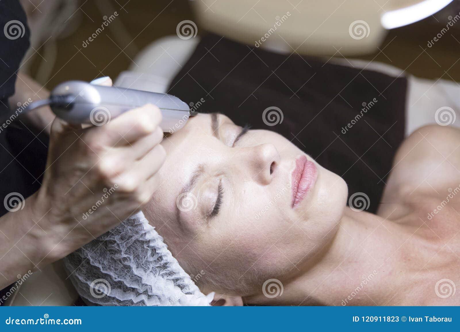 Zbliżenie portret szczęśliwa młoda kobieta i ręka z kosmetycznym podnośnym przyrządem dotyka jej twarz