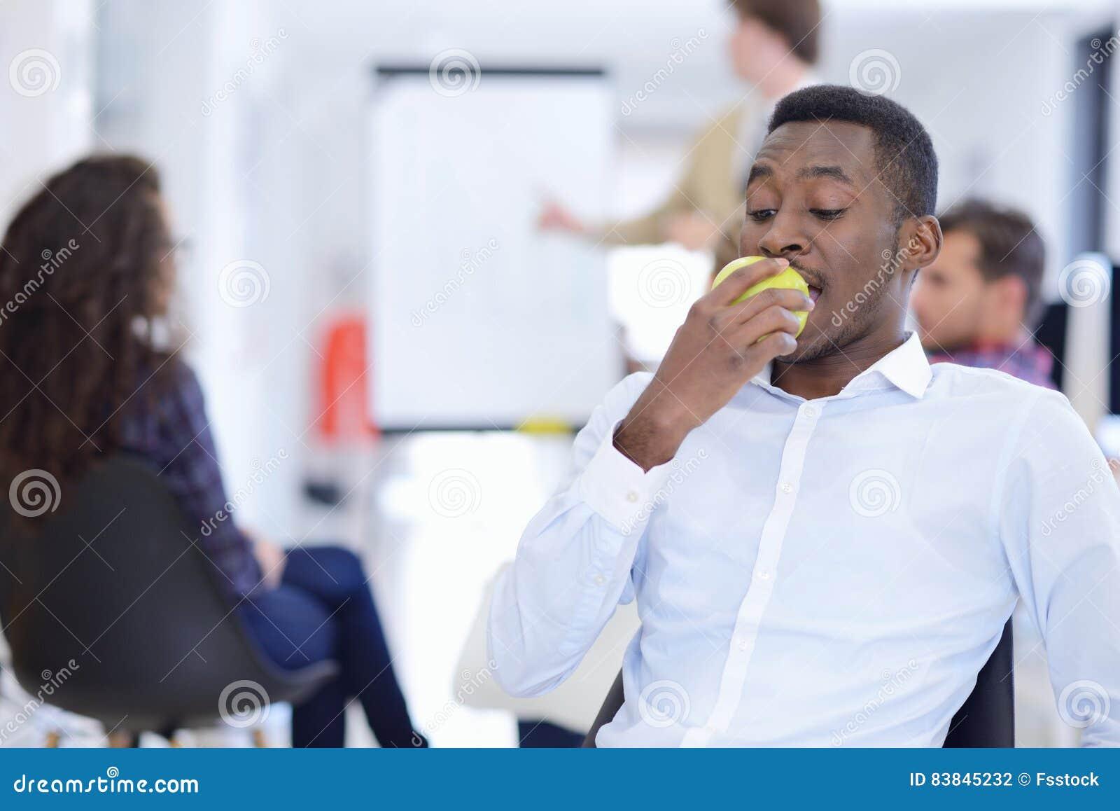 Zbliżenie portreta poważny biznesowy mężczyzna, dylowy producenta łasowania zieleni jabłko