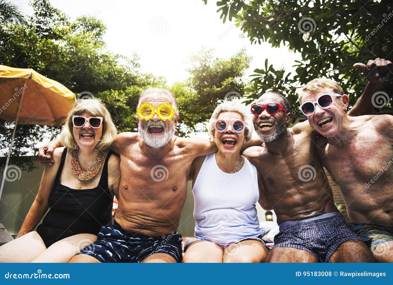 Zbliżenie różnorodni starsi dorosli siedzi basenem cieszy się su