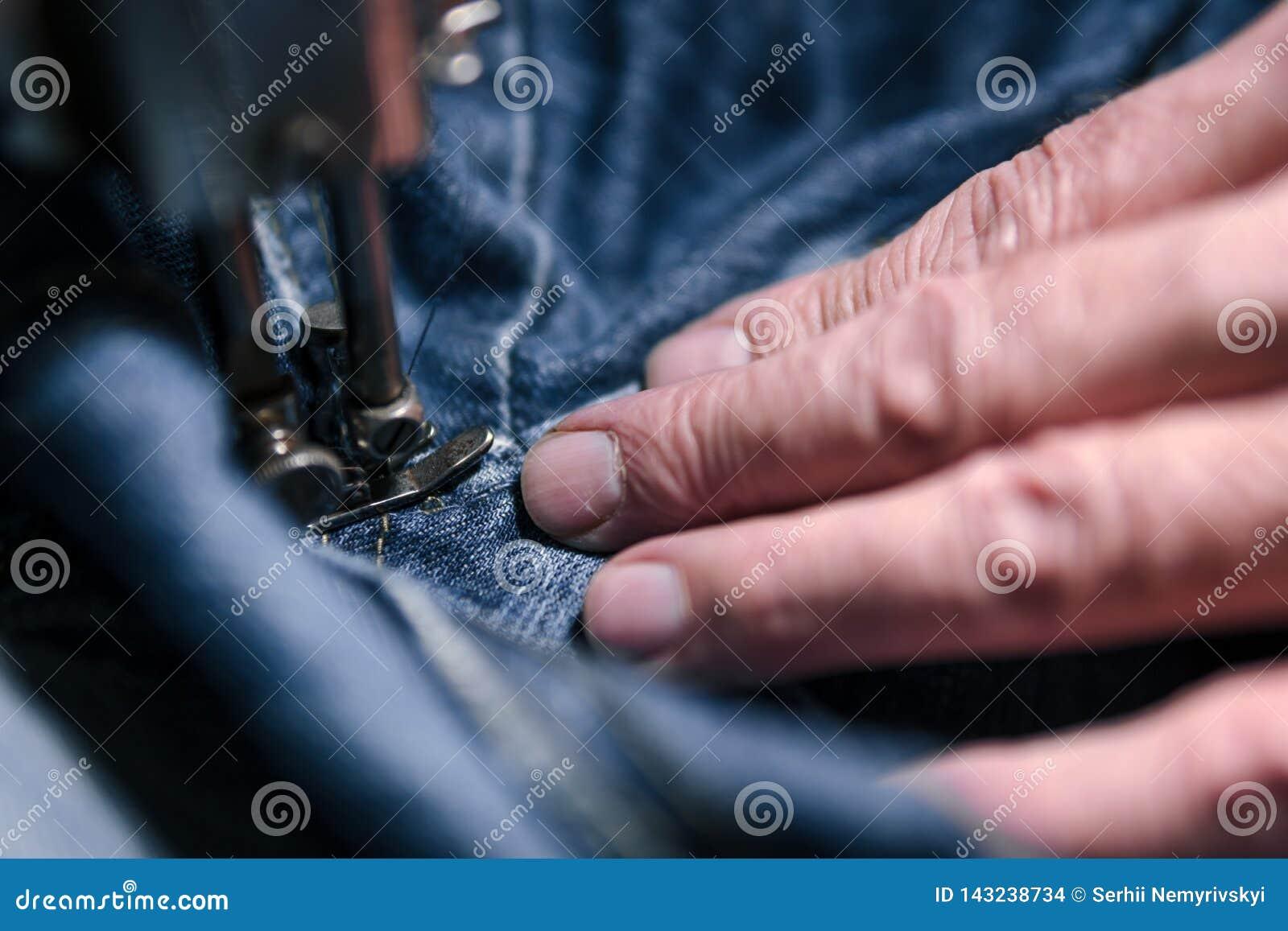 Zbliżenie ręki pracuje na starej szwalnej maszynie Krawiecki mężczyzna cajg tkaniny sukienna tkanina w sklepie, krawiectwo, zakoń