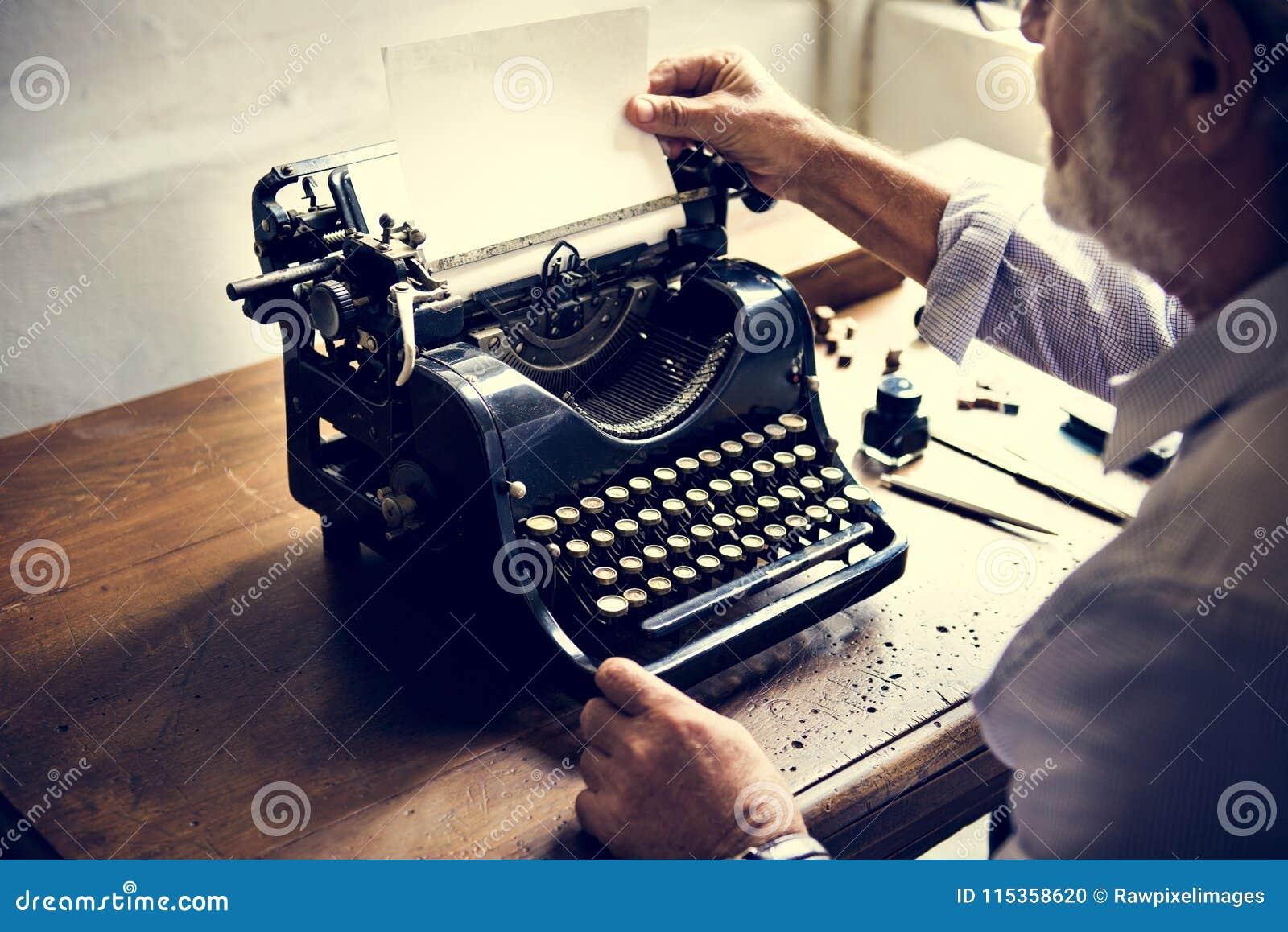 Zbliżenie ręki zmienia papier na rocznika maszyna do pisania