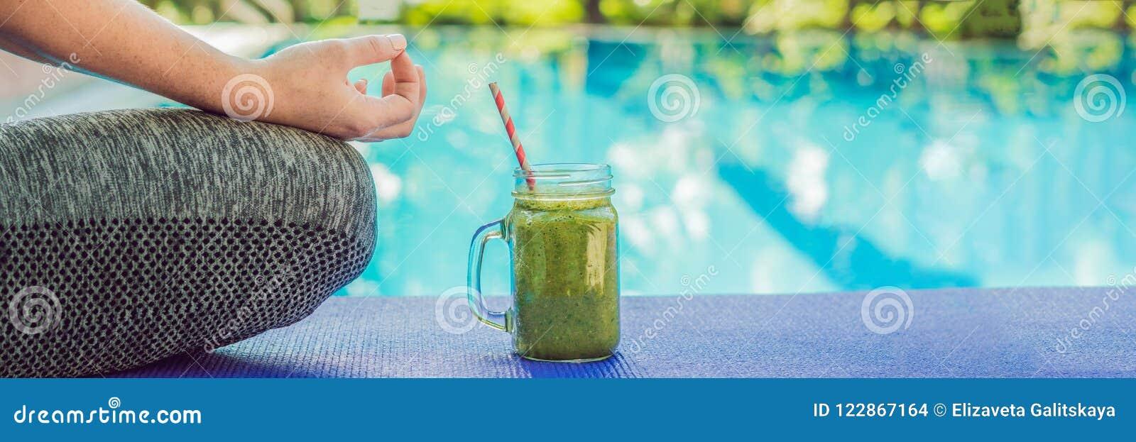Zbliżenie s kobiety ` ręki podczas medytaci z zieleni smoothies szpinak, pomarańcze i banan na tle basenu b,