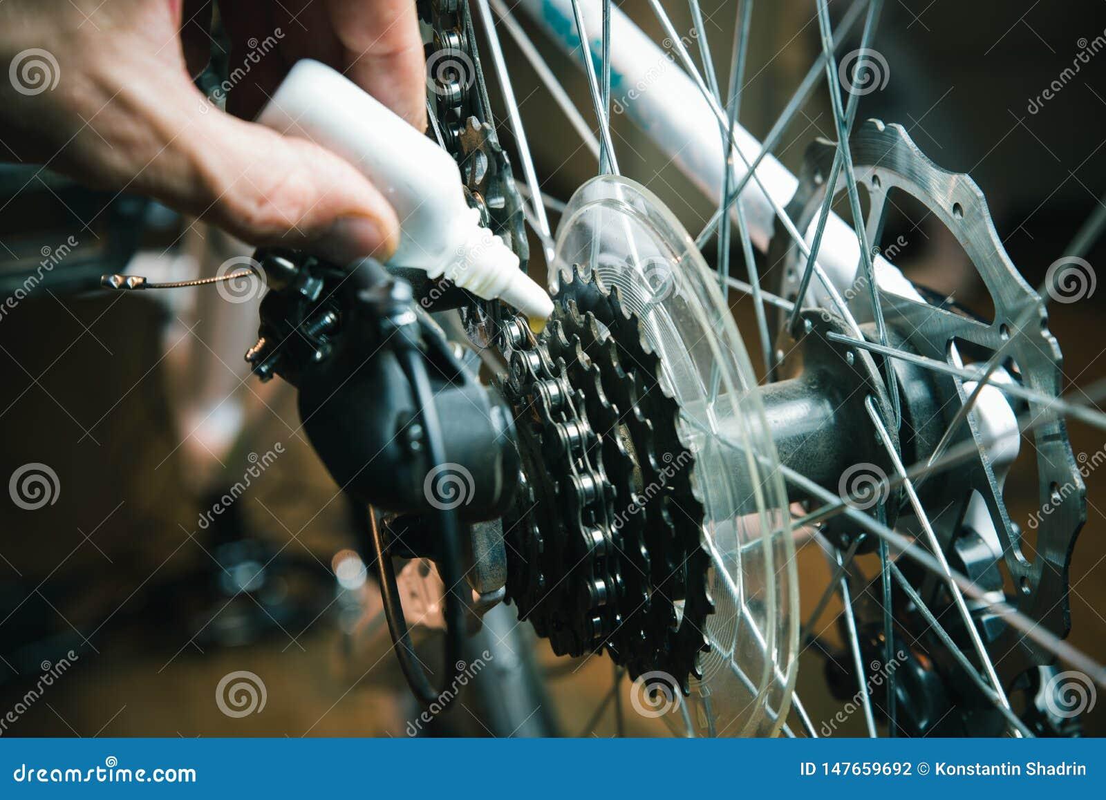 Zbliżenie samiec ręki czyści bicykl przekładnię i oliwi łańcuch z nafcianą kiścią i Pracuj?cy proces