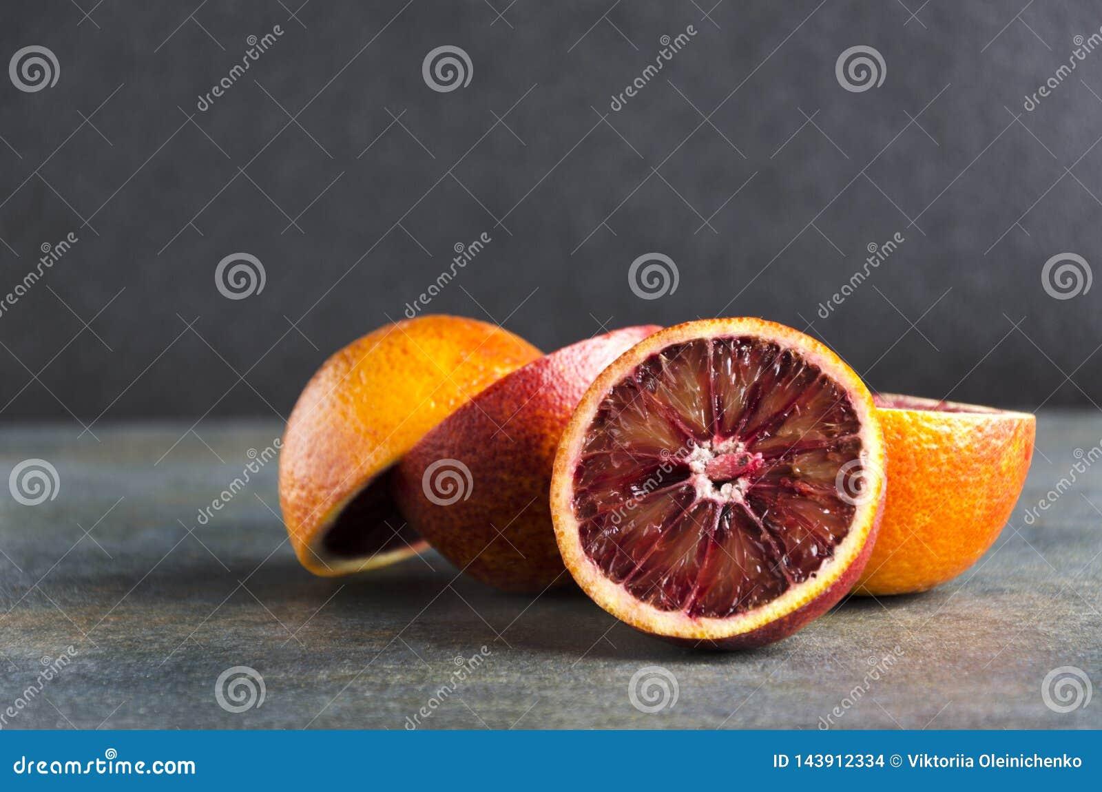 Zbliżenie stos krwionośna pomarańcze na popielatej powierzchni przeciw czarnemu tłu