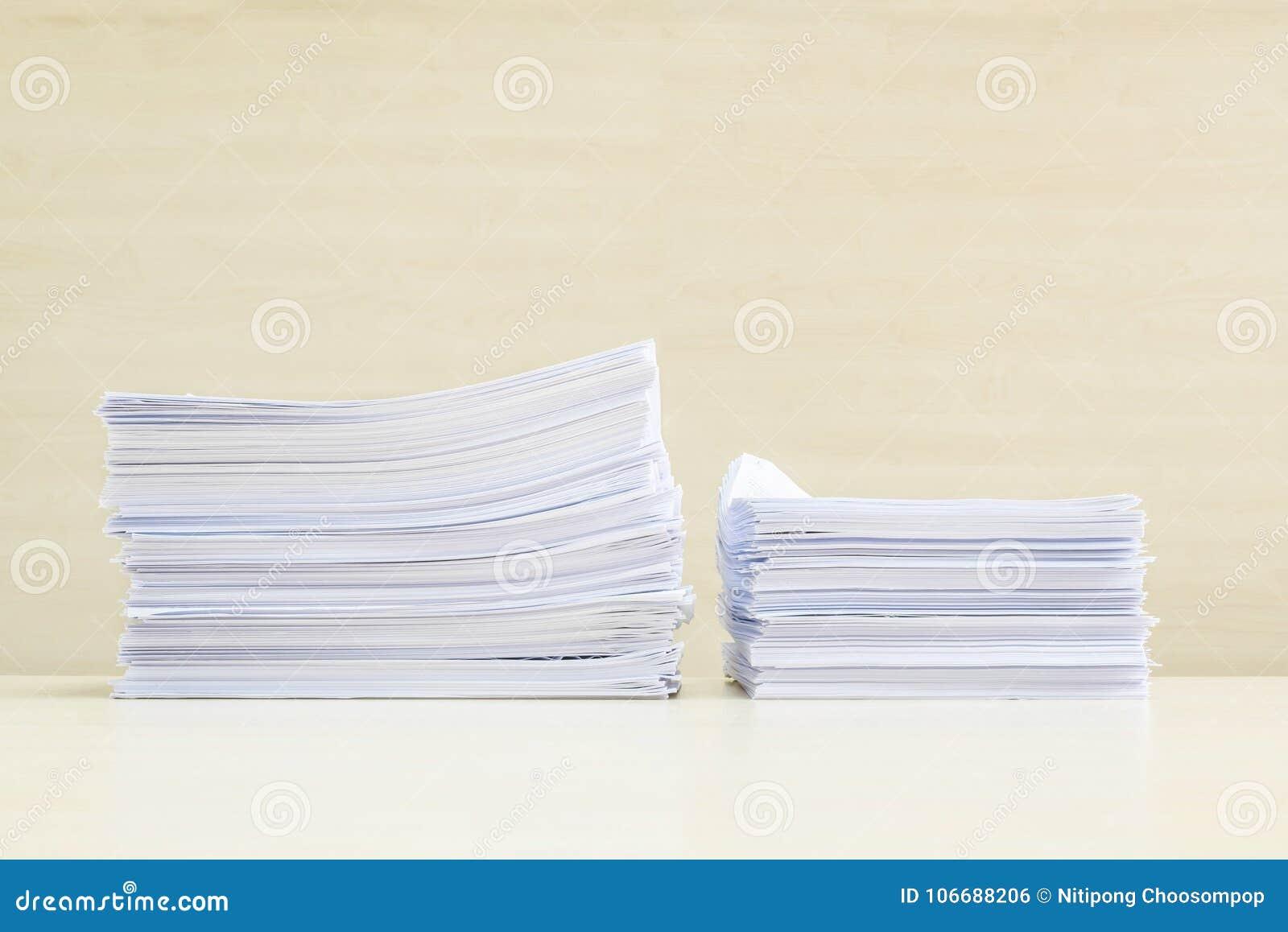 Zbliżenie stos praca papier na zamazanym drewnianym biurku i ściana textured tło w pokoju konferencyjnym pod okno światłem, ciężk