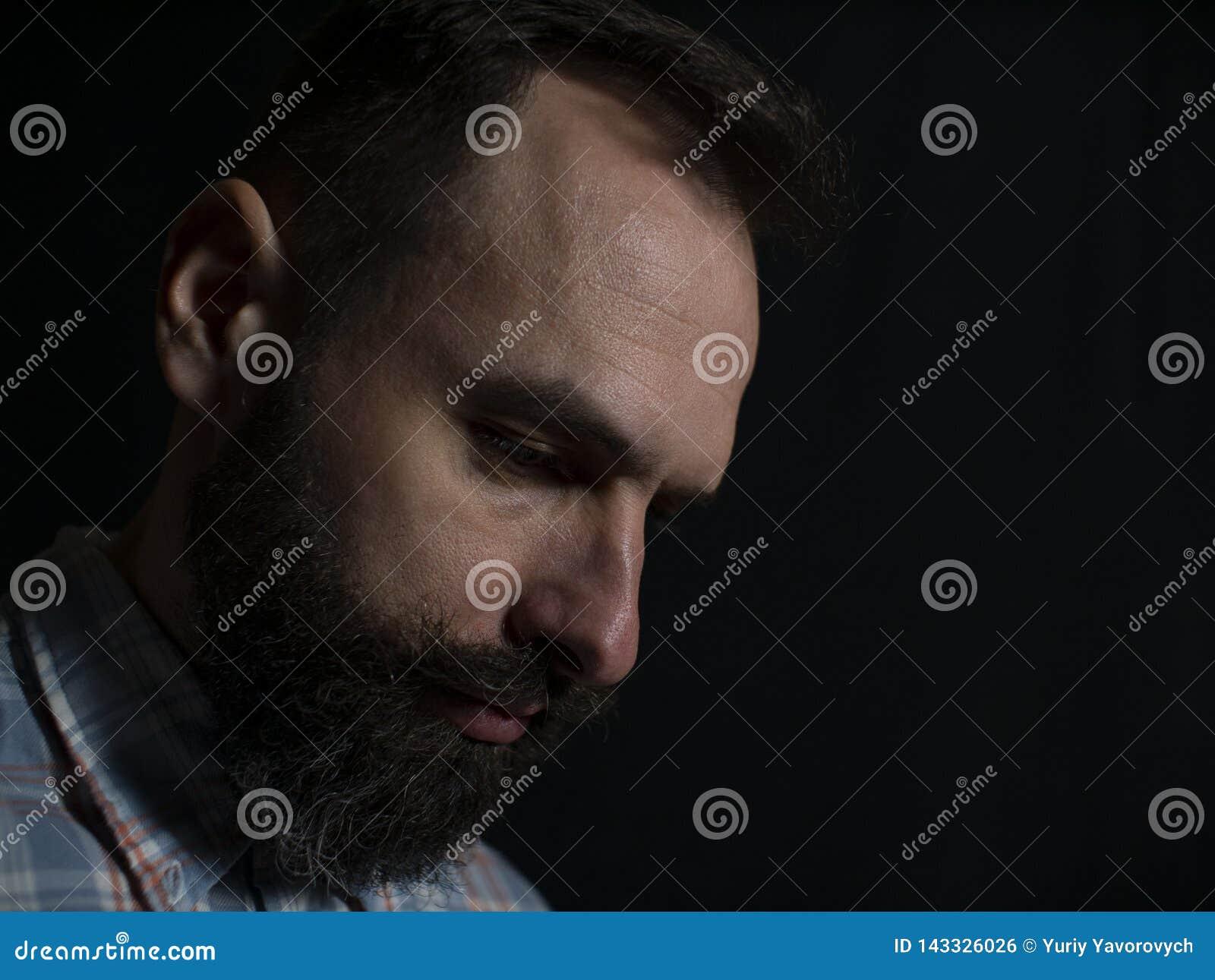Zbliżenie twarz elegancki mężczyzna patrzeje w dół na czarnym tle z brodą i wąsy z poważną twarzą