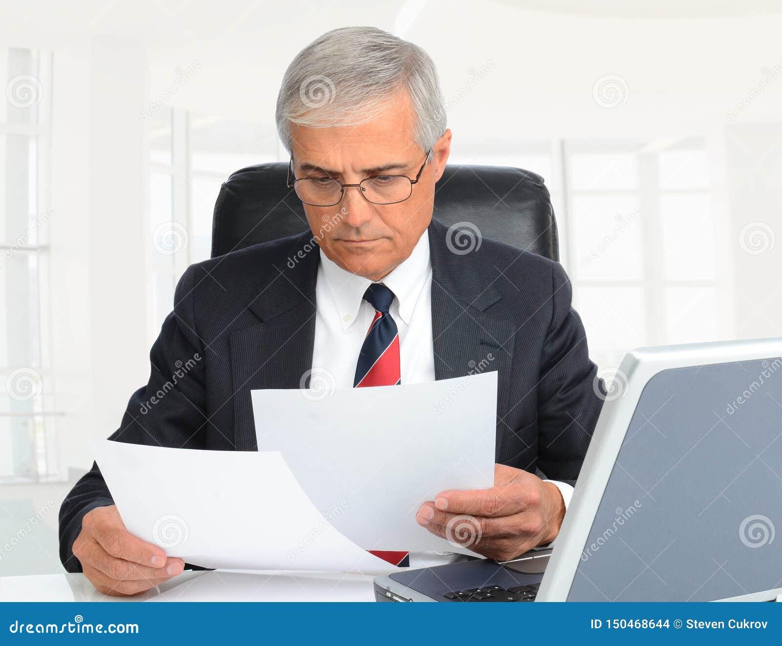 Zbliżenie w średnim wieku biznesmena obsiadanie przy ten biurkiem patrzejący dokumenty w nowożytnego wysokość klucza biurowym poł