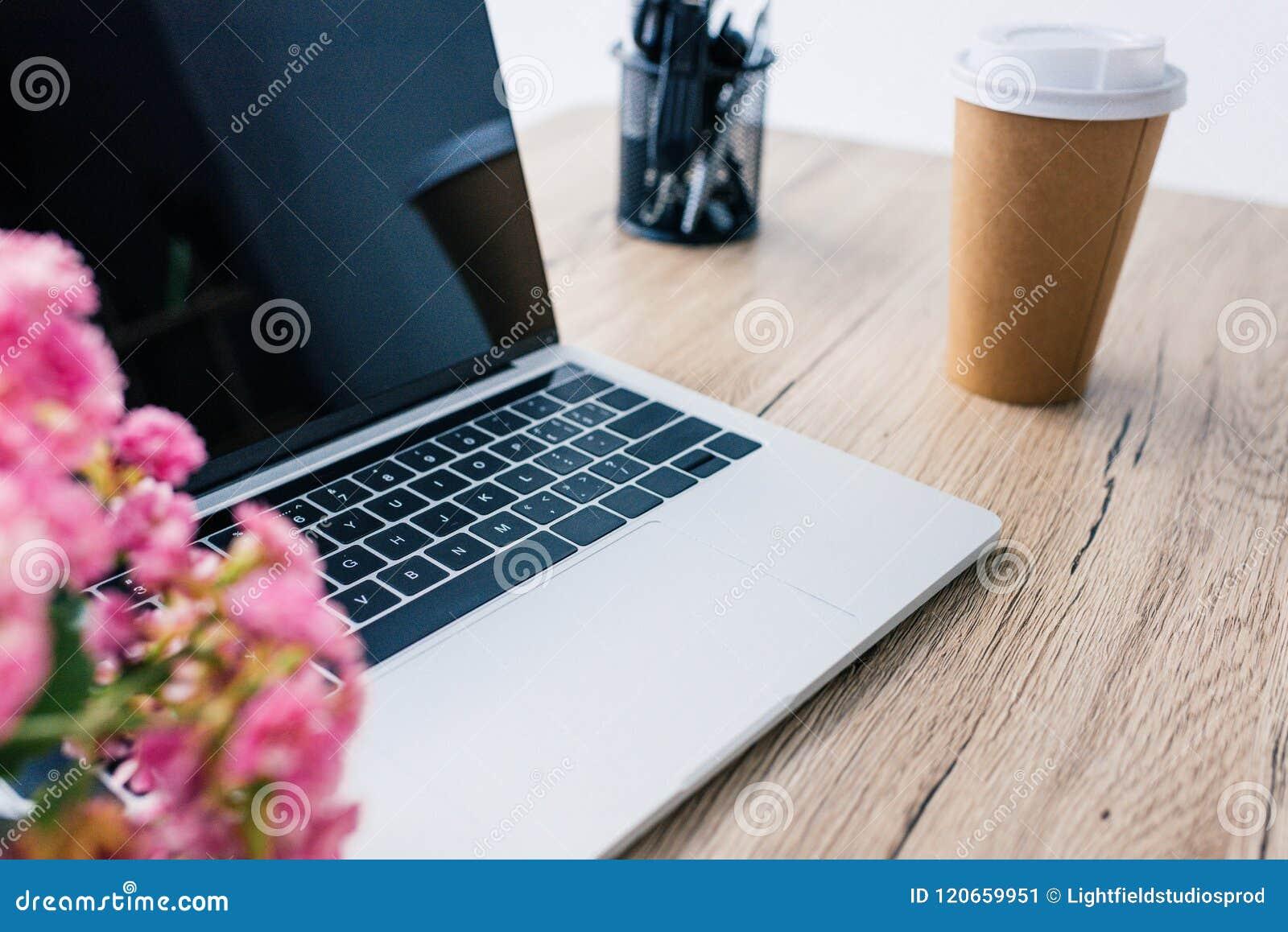 Zbliżenie widok laptop z pustym ekranem, kwiatami, papierową filiżanką kawy i materiały,