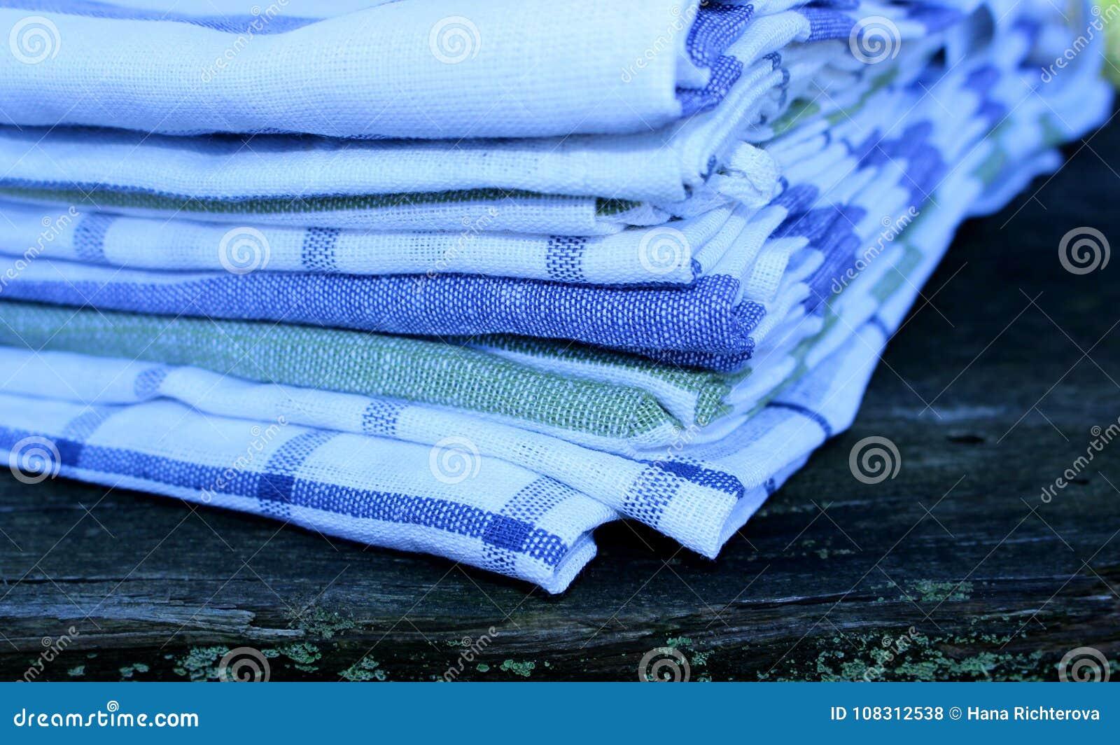 Zbliżenie widok na ustaleni kuchenni ręczniki na drewnianym tle w naturze zamazujący tło