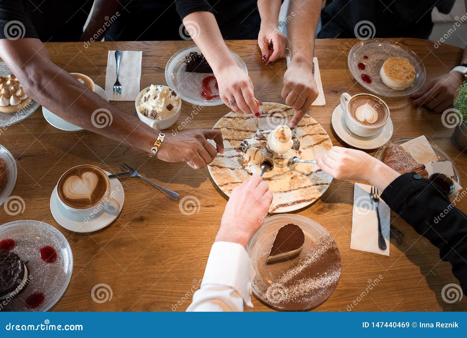 Zbli?enie multiracial r?ki z deserami i fili?ankami w kawiarni